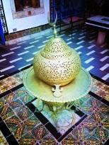 Une lanterne magnifiquement ouvragée sur un plateau de cuivre au centre de la cour intérieure